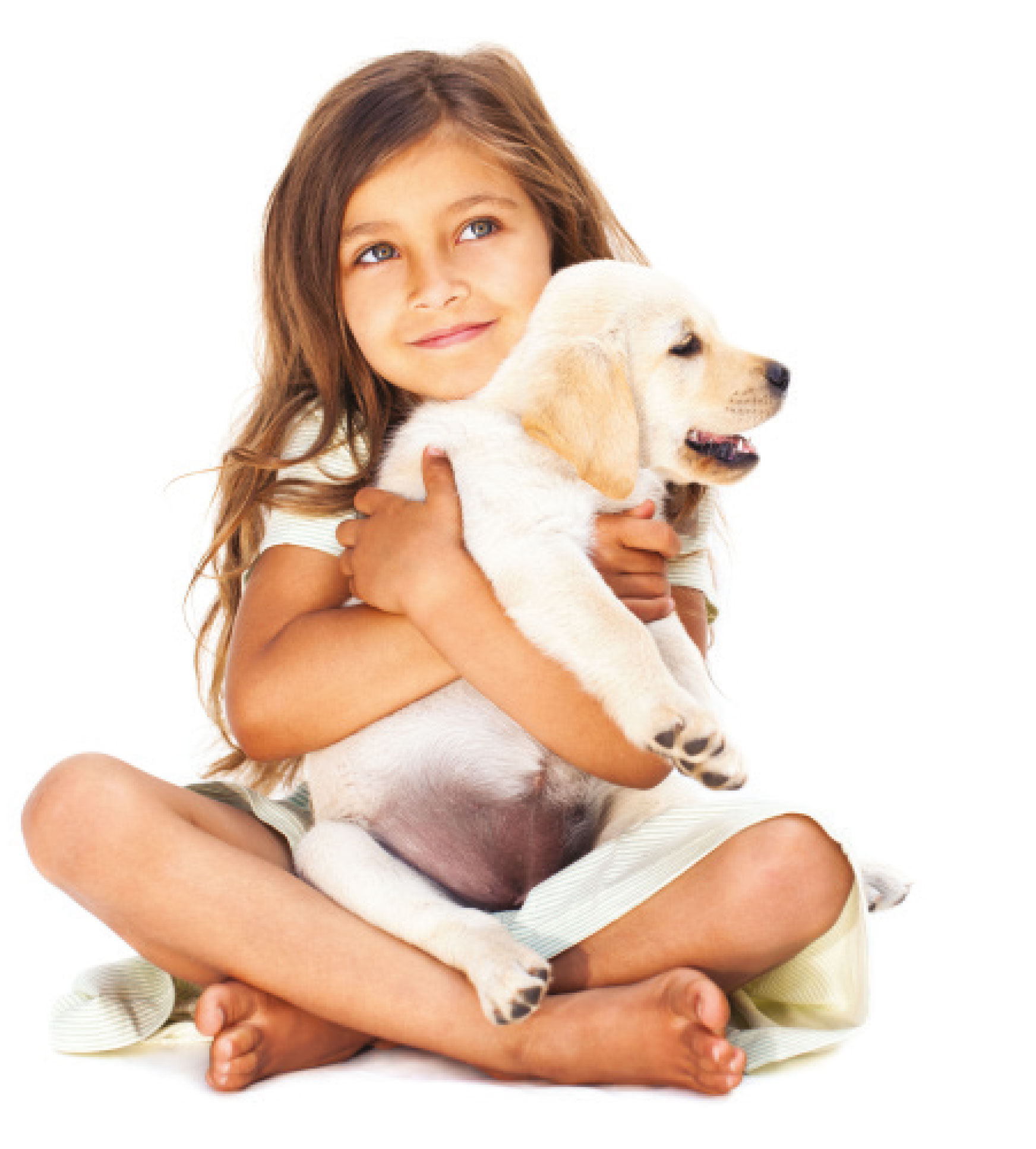 A young girl sitting cross legged on the floor cuddling a labrador puppy